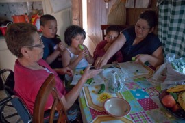 Eloisa Lara, 65, (left) had her right leg amputated due to complications with her diabetes. Sandra Cerda, 41, cuts some cucumbers for her son Erick Torres, 3, and his cousins Kayla Ramirez, 5, and Issac Ramirez, 7. (Photo: Michel Duarte/Walter Cronkite School of Journalism and Mass Communication)